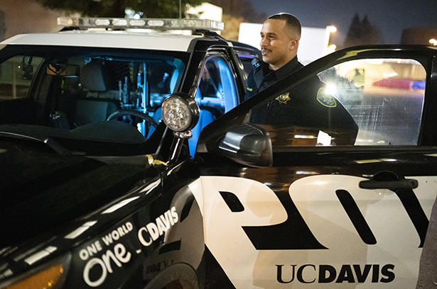 UC Davis officer stands with door to marked Police car open