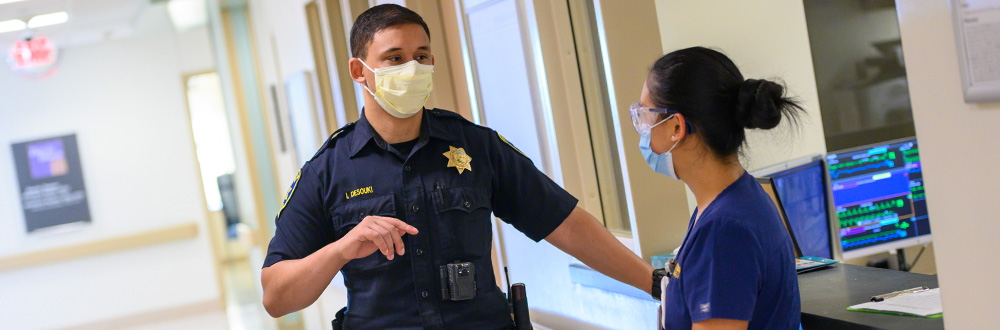 Police officer talks to nurse at the UC Davis medical center