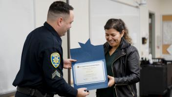 UC Davis alumnus grinning as she shakes police officer's hand and gets certificate