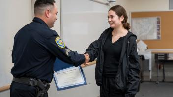 young woman in tracksuit shakes the hand of police officer, as he hands her certificate