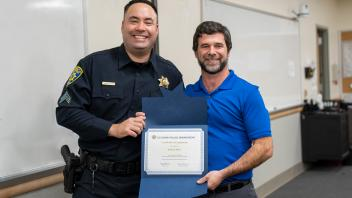 UC Davis police officer with staff member and certificate, smiling