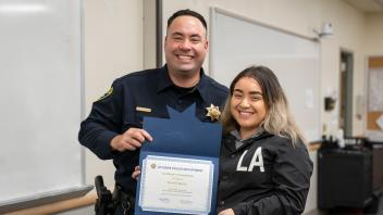 Police officer with UC Davis student and certificate, smiling