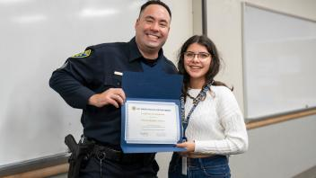 UC Davis students with police officer and certificate, smiling