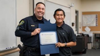 UC Davis police officer with student and certificate, smiling