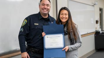 UC Davis staff member with campus police officer and certificate, smiling