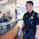 Officer smiles as he approaches a desk at UC Davis Health in Sacramento