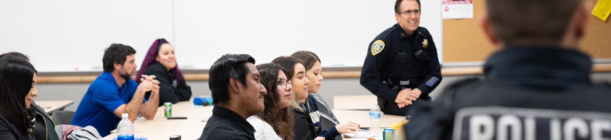 Police captain smiling with students listening in a classroom