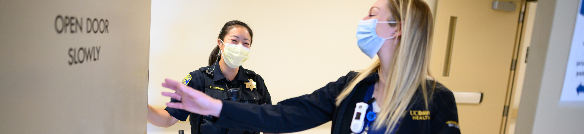 Female officer and nurse with face coverings walk through UC Davis Medical Center