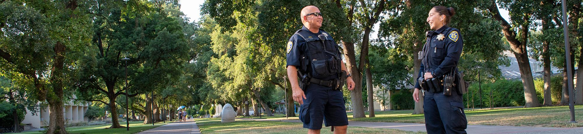 Police officers talk and laugh near Mrak Hall at UC Davis Campus