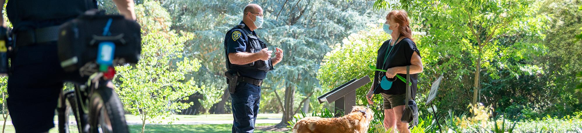 Officer and visitor with her dog talk in the arboretum while wearing face coverings