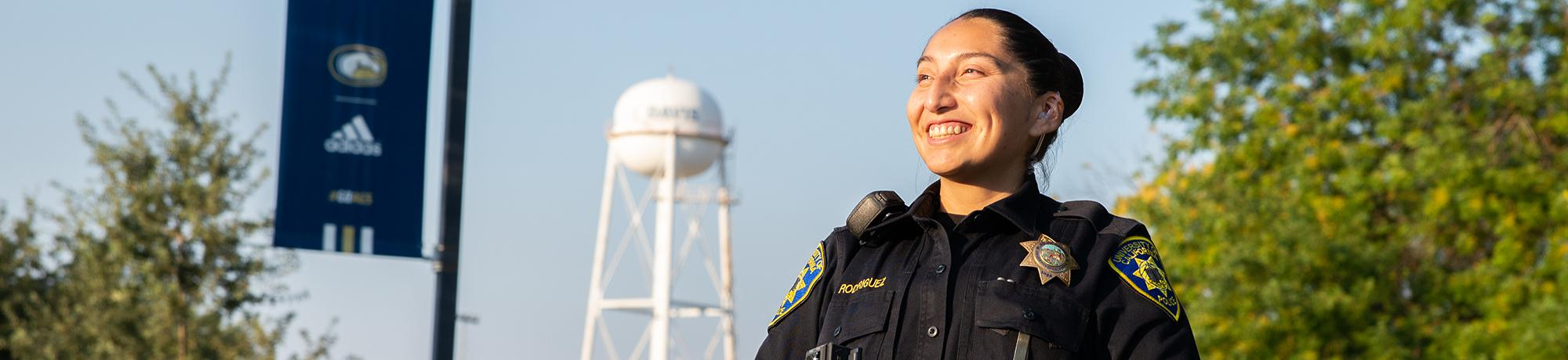 Officer smiles with UC Davis water tower in the background